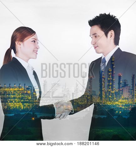 double exposure of shaking hand between businessman and businesswoman with industrial oil refinery plant background