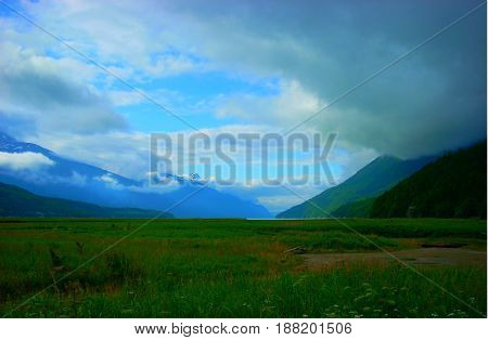 green valley between mountains with blue sky