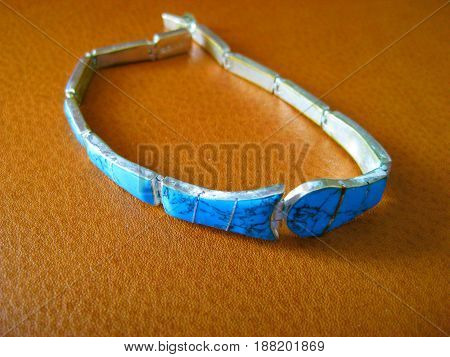 Silver and blue bracelet on leather setting