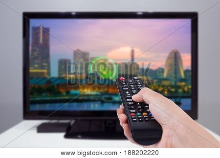 Hand Holding Tv Remote Control With A Television And City Screen In Background