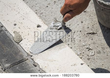 Construction worker leveling concrete pavement outdoors - focus is on the tool.