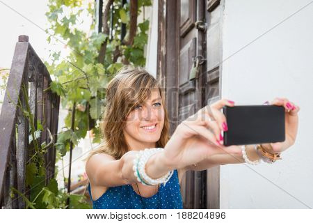 Cute girl using cellphone in front of a old house.