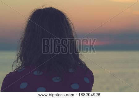 Lonesome girl watching the dawn / dusk over sea / ocean horizon.