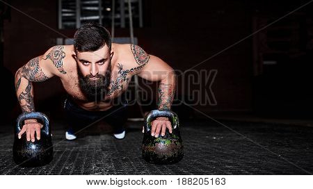 Strong, Handsome Man Doing Push-ups On Dumbbells In A Gym As Bodybuilding Exercise, Training His Mus