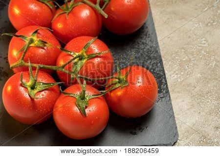 Bunch Of Red Ripe Wet Tomatoes On The Black Stone Board