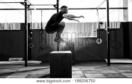 Fit young man jumping onto a box as part of exercise routine. Man doing box jump in the gym. Athlete is performing box jumps