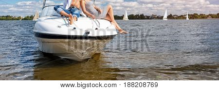 Love couple or friends relaxing on a yacht, enjoying sun on sunny summer day. Legs hanging from the boat floating on the river. Vacation holidays, romantic theme. Banner for website.