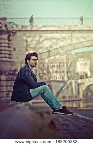 Handsome young man sitting in the city center. Relaxing and thinking in urban scenery. Fashionable clothes, blue jacket and jeans. Glasses. Bridge and city life in the distance. Rome, Italy.