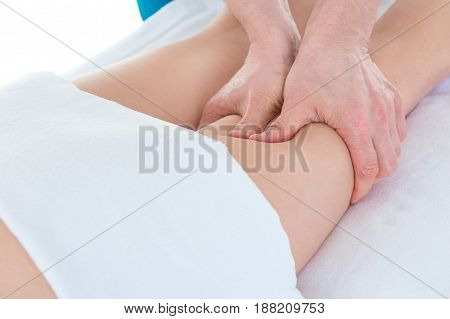 Leg massage. Therapist doing massage of legs at clinic applying strong finger pressure