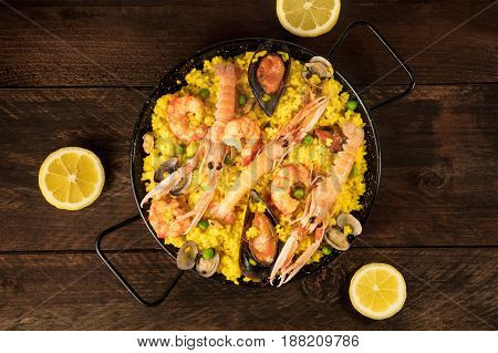 A photo of a Spanish seafood paella in a typical paellera, with mussels, clams, and shrimps, lemon wedges, and a place for text, shot from above on a dark rustic texture