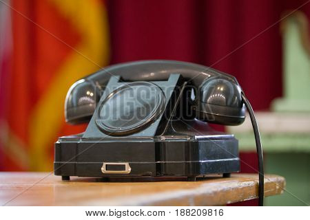 black vintage telephone on old table on red background