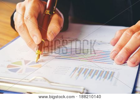 Hand With A Pen Writing On The Business Paper. Report Chart