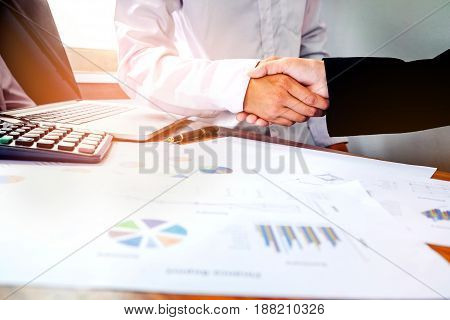 Two Business People Shaking Hands While Sitting At The Working Place