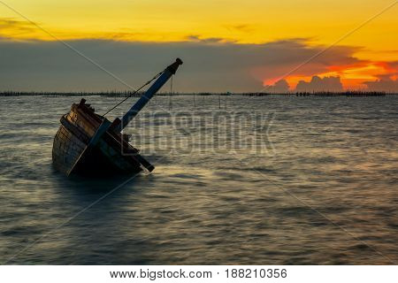 Shipwreck on the beach in beautiful sunset.