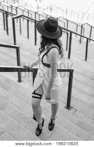 Young beautiful sexy woman wearing trendy outfit, white dress, black hat and leather swordbelt. Longhaired brunette posing in the city street. Outdoor fashion photography.