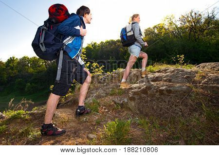 a couple hiking in the forest. Couple backpackers hiking on the path during summer. Travel hiking backpacking tourism and people concept