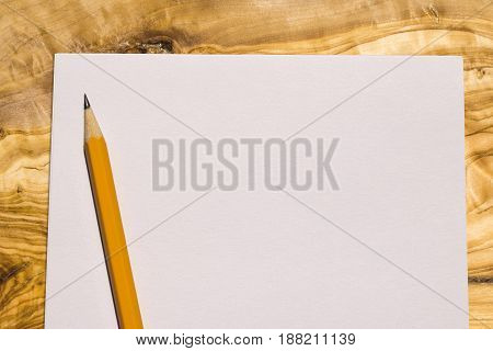 aerial view of a sheet of paper with a yellow pencil on a wooden desk