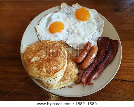 American Breakfast double fried eggs Bacon and sausages serve with butter pancake on white plate on wooden table