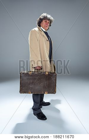 The senior man in cloak as detective or mafia boss. Studio shot on gray in retro stile. Mature man with hat and suitcase