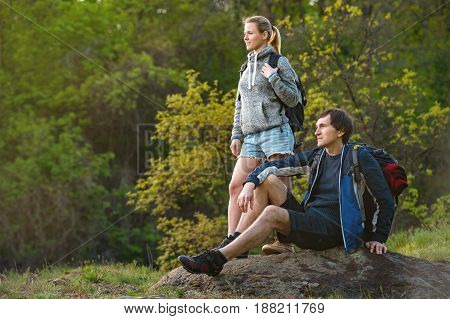 Woman and man with backpacks walking on the forest and mountain and enjoying the nature. Couple resting. Travel vacation holidays and adventure concept.