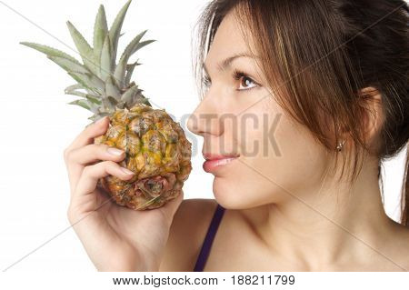 studio portrait of young pretty woman holding pineapple isolated against white background