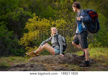 Hikers with backpacks resting on the way to rocks. Travel vacation holidays and adventure concept. Forest Mountain landscape background