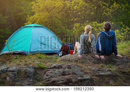 couple of hikers with backpacks resting near the tent in the warm sunshine at sunset. Travel vacation holidays and adventure concept. Forest Mountain landscape background