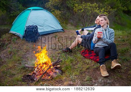 Young happy couple hiking in forest. Smiling couple resting enjoying a break during hike vacations. Camping travel tourism hike and people concept.