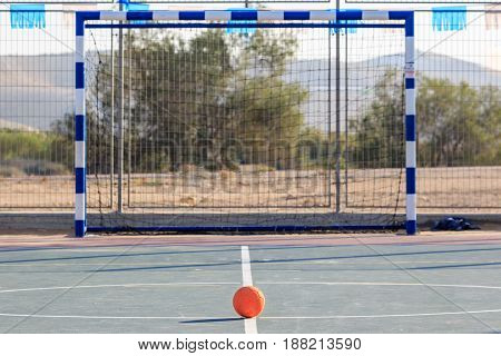 Children's rubber soccer ball front of gates on the court