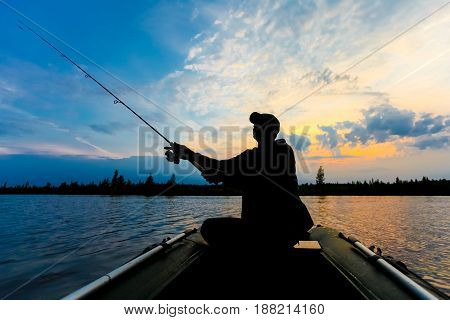 Fisherman silhouette with fishing rod in the inflatable boat at sunrise and throws a lure for catching fish