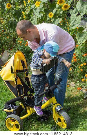 Parents help the boy sit on a bike