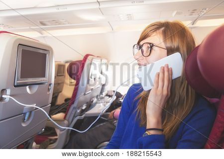 Girl using cellphone / smartphone in the airplane.