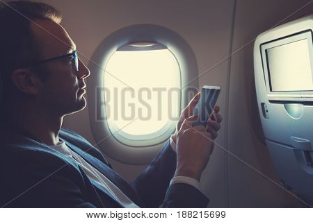 Man using smartphone / cellphone in the airplane.