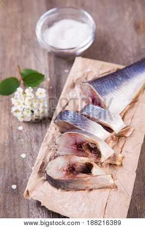 fresh raw herring on paper with salt and flower in studio