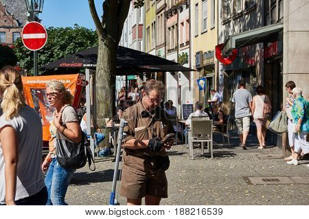 DUESSELDORF, GERMANY - AUGUST 17, 2016: Unidentified parcel service clerk checks data on his mobile device in the Altstadt of Duesseldorf