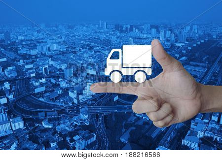 Truck delivery icon on finger over modern city tower street and expressway Transportation business concept