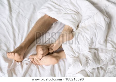 Barefoot legs of lovers under the white blanket on the bed. Indoors. Closeup. Horizontal.