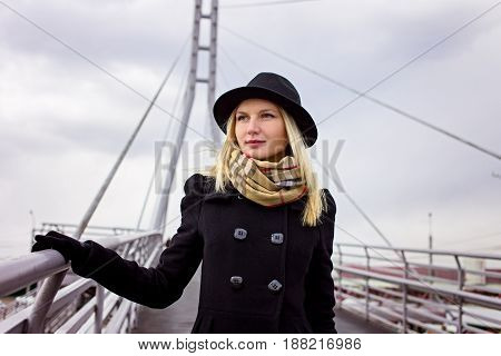 Portrait of young gorgeous blonde women in black coat and hat on a river bridge in cloudy autumn or spring day