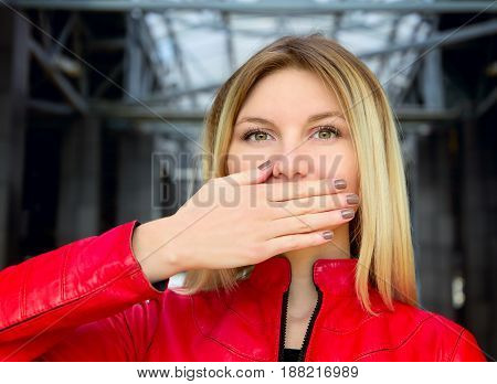 Beautiful young blond woman covering face with her hand. Emotional female portrait.