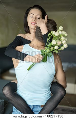 Cute hugging couple in the bedroom. Smiling girl with closed eyes in a black shirt and dark stockings is embracing her boyfriend with the legs and hands. She holds a bouquet of flowers in right hand.