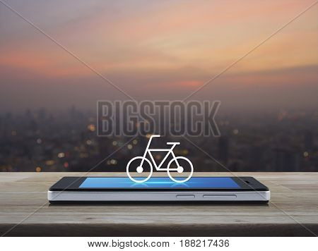 Bicycle flat icon on modern smart phone screen on wooden table over blur of cityscape on warm light sundown Bike shop online concept