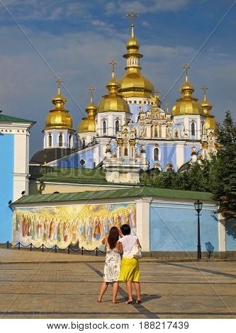 Two women in summer dresses looking at the St. Michael's Cathedral in Kiev. View from the back. Cathedral of St Michael's Golden-Domed Monastery, decorated with murals.