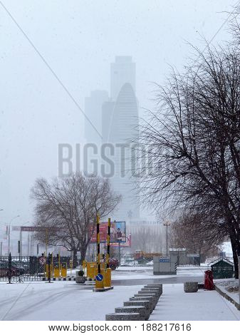 MOSCOW - RUSSIA - MARCH, 2011: View from the car park at the Expocenter building in Moscow. Snowy, dank weather, early spring. Skyscraper in the fog. Vertical photo.