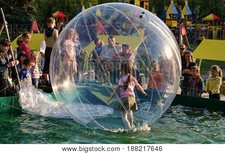 KIEV - UKRAINE - JULY, 2009: Children are playing near the inflatable pool on the playground. The girl is in a transparent inflatable balloon on the water. Children look at her and laugh