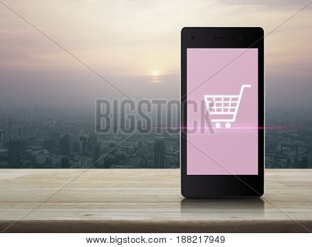 Shopping cart icon on modern smart phone screen on wooden table over city tower at sunset vintage style Shop online concept