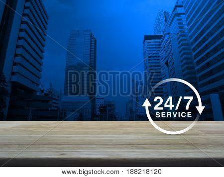 24 hours service icon on wooden table over modern office city tower background Full time service concept