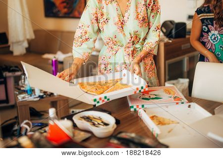 Girls in dressing gowns ordered pizza. Opening a box of pizza and tearing off the first piece.