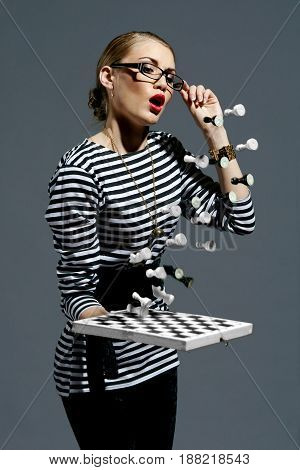 Fashion style vogue portrait of young pretty female model posing with chess. Flying figures