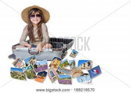 Long haired little girl with straw hat is sitting in a open suitcase. Photos of the sights of Provence (France) flies around the suitcase. All is on the white background. Horizontally.