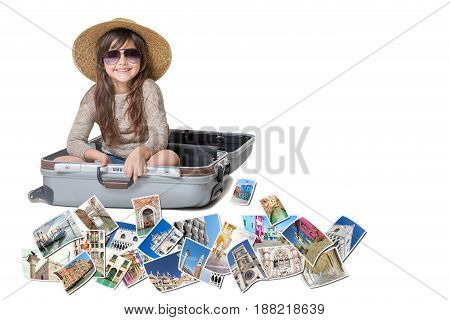 Long haired little girl with straw hat is sitting in a open suitcase. Photos of the sights of Venice (Italy) flies around the suitcase. All is on the white background. Horizontally.